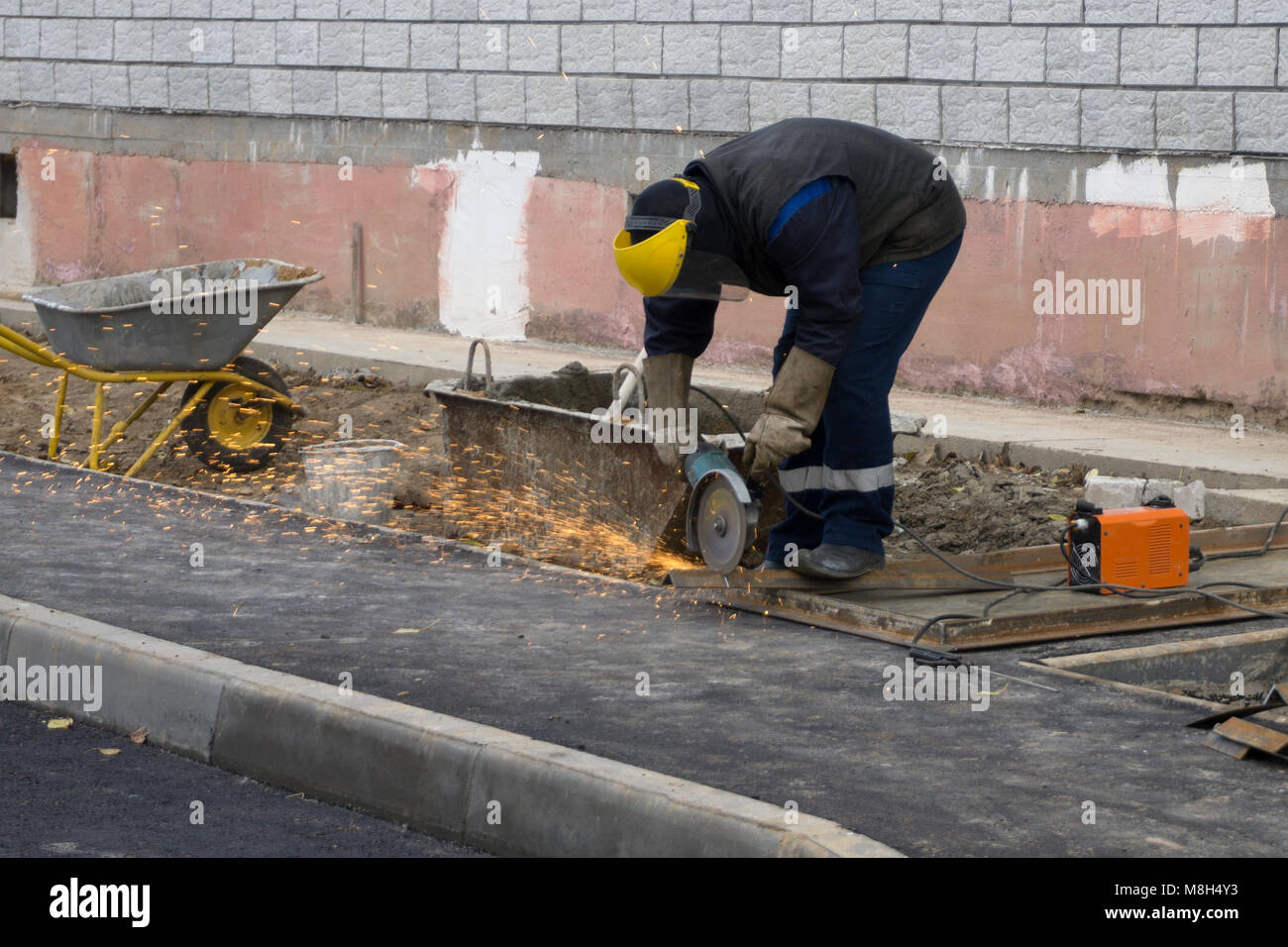 Close up of trained worker in protective workwear, gloves and glasses using angle grinder to smooth metal of profile - Stock Image