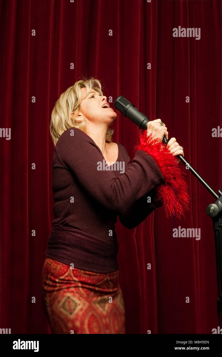 Singer on stage with microphone. - Stock Image