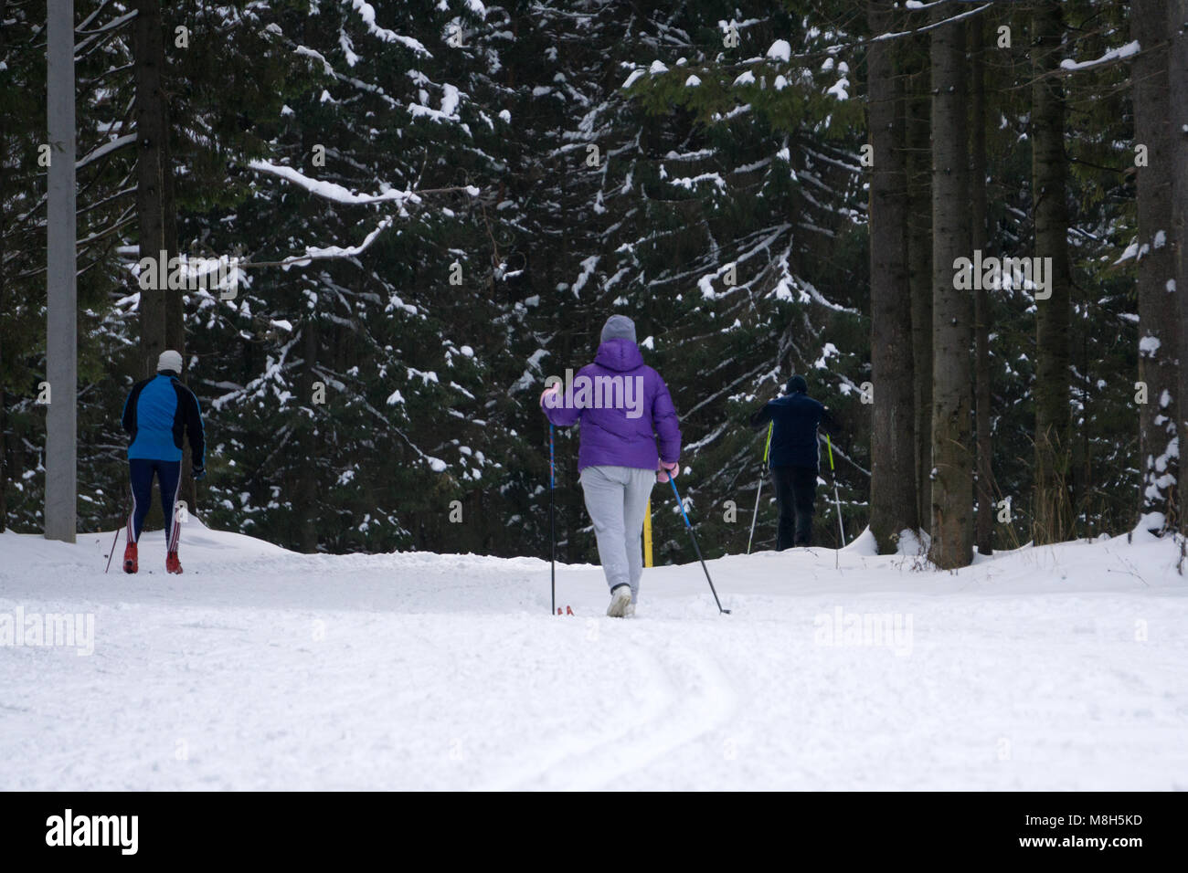 in ski suits on vacation. Young man girl . Girl walking on the trail - Stock Image