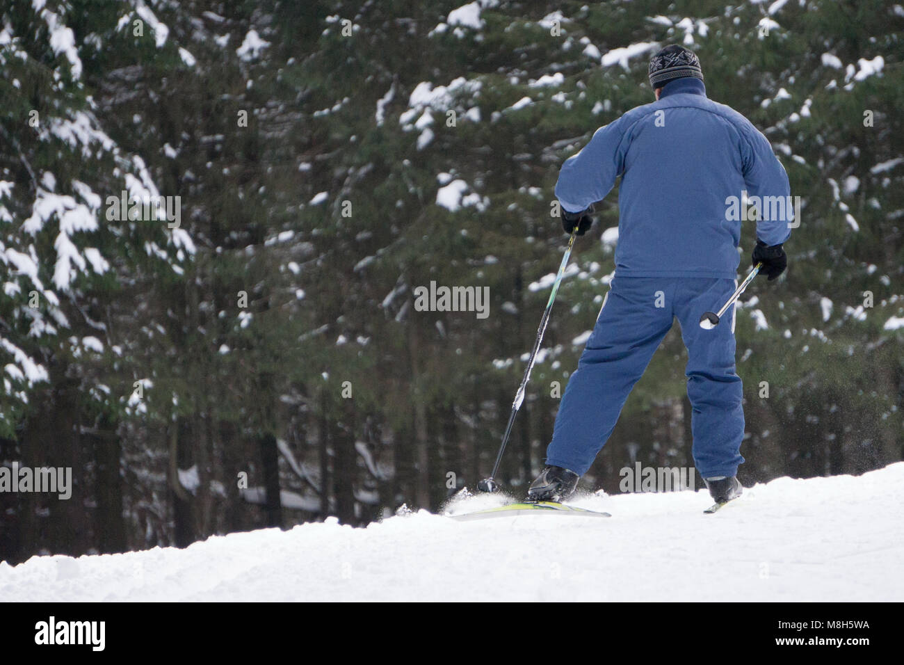 Boy skier in a ski suit and hat standing on snowy slope - Stock Image