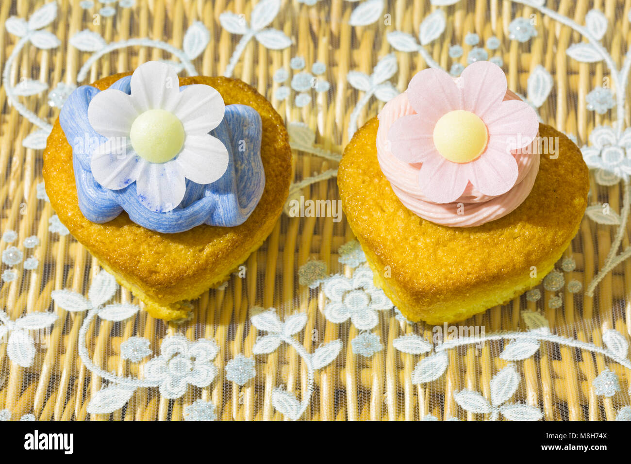 home made heart shaped cupcake cakes, one with strawberry pink frosting icing and one with blue, and rice paper - Stock Image