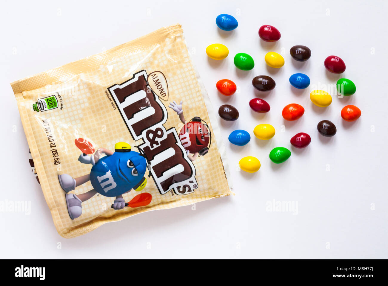 Travel Retail Edition bag of Almond M&Ms with contents spilled on white background - Stock Image
