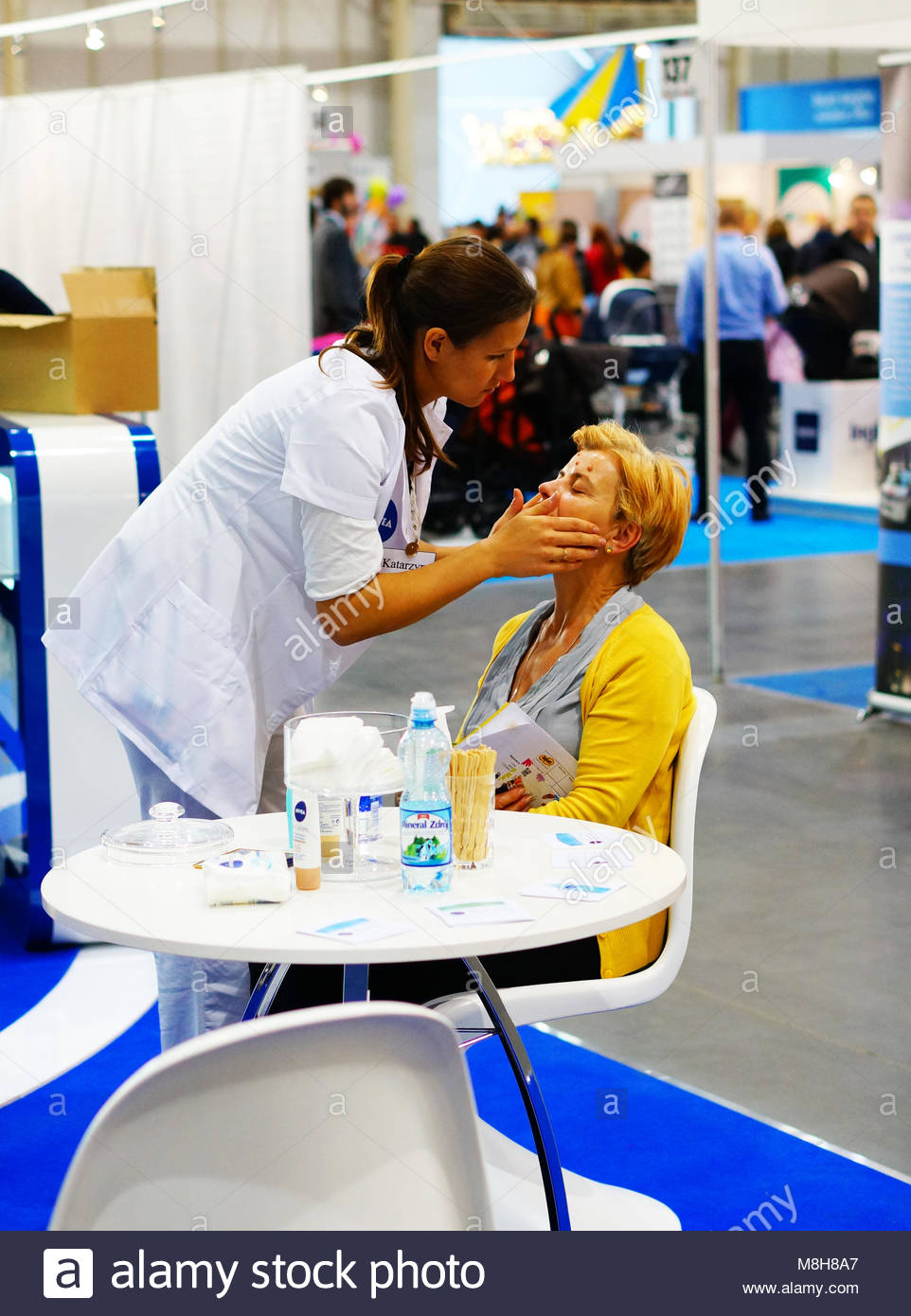 POZNAN, POLAND - OCTOBER 19, 2013: Woman having a face treatment at a Nivea stand in a fair trade - Stock Image