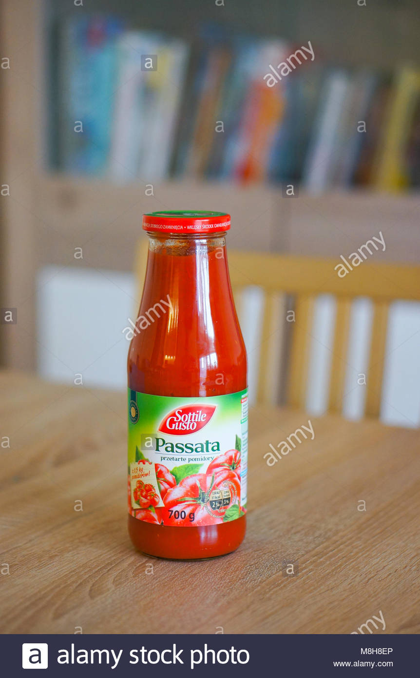 POZNAN, POLAND - MARCH 31, 2016: Sottile Gusto passata in a glass bottle standing on wooden table - Stock Image