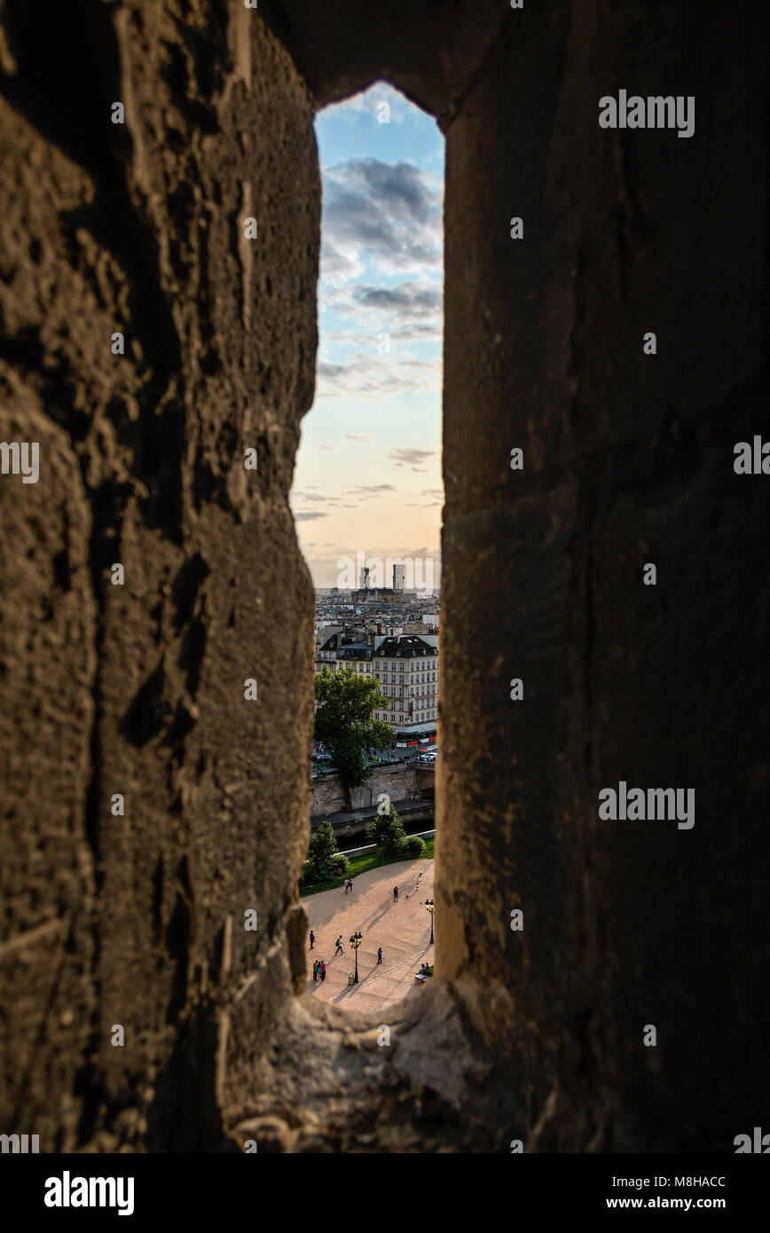 Narrow window in stone wall with view of beautiful Paris cityscape in clouds Stock Photo