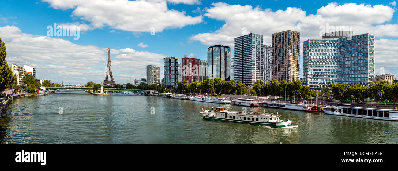 Panoramic view of modern district placed on embankment of Sena river in old Paris city against blue sky - Stock Image