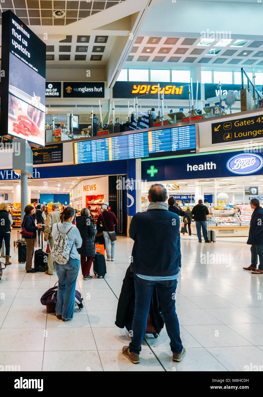 London Gatwick, March 15th, 2018: Passengers check their flight information on a digital display at London Gatwick's - Stock Image