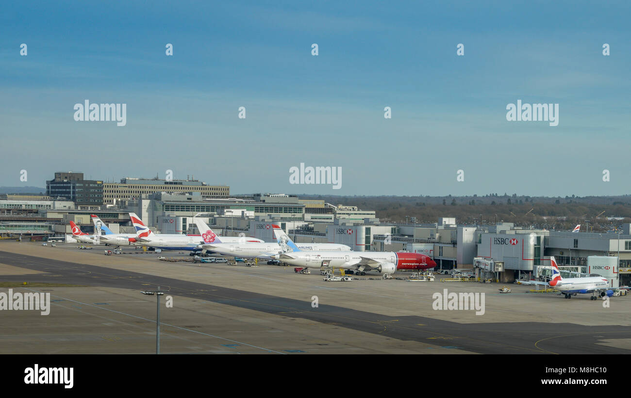 London Gatwick, March 15th, 2018: Airplanes of different airliners on tarmac awaiting passengers at London Gatwick's - Stock Image