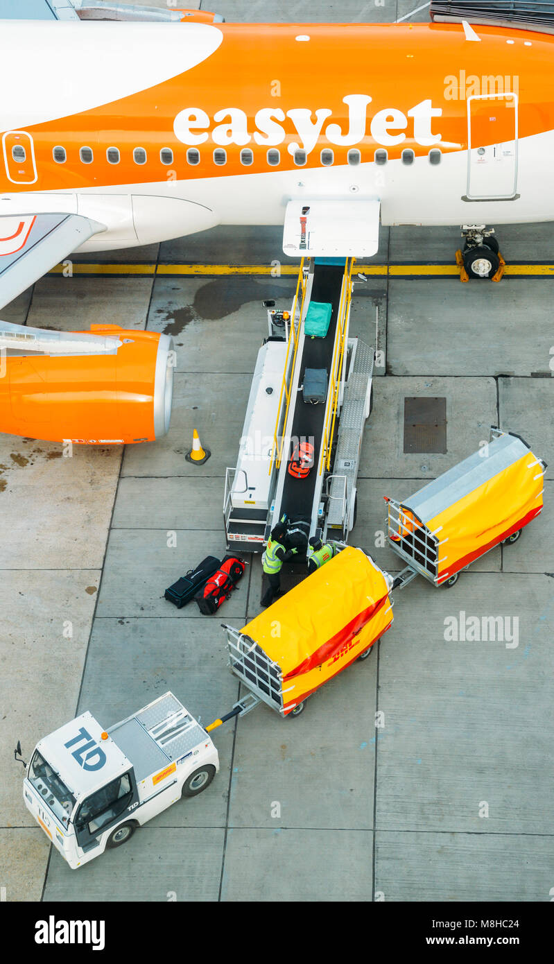 High perspective of baggage handlers picking up suitcases from a conveyor belt connected to an Airbus A320 easyJet - Stock Image