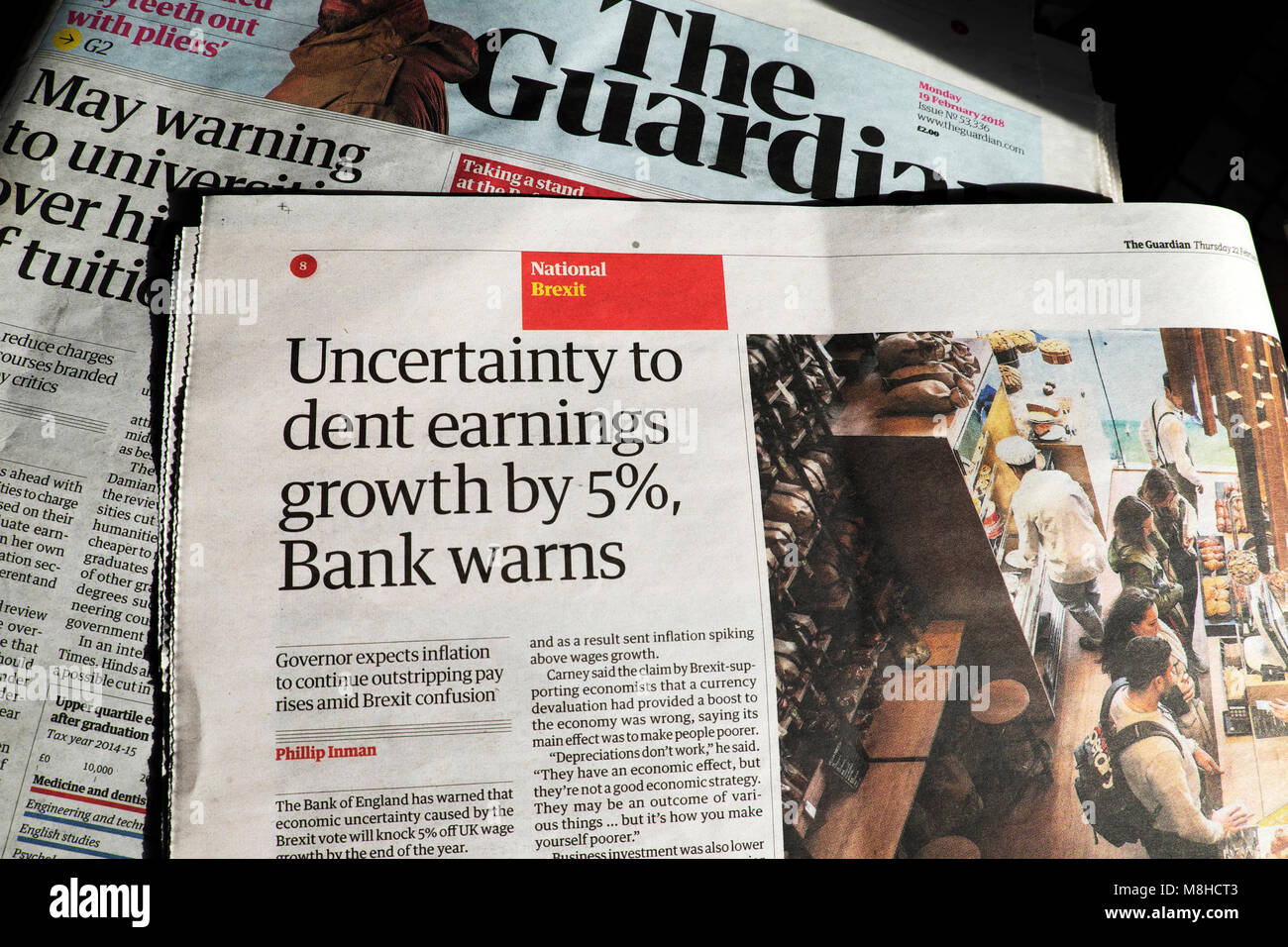 Guardian newspaper article headline 'Uncertainty to dent earnings growth by 5% Bank warns' London England - Stock Image