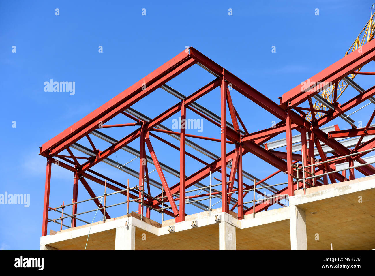 Building construction in progress. Red primer painted steelwork. Rolled steel joists rsj framework. Blue sky space - Stock Image