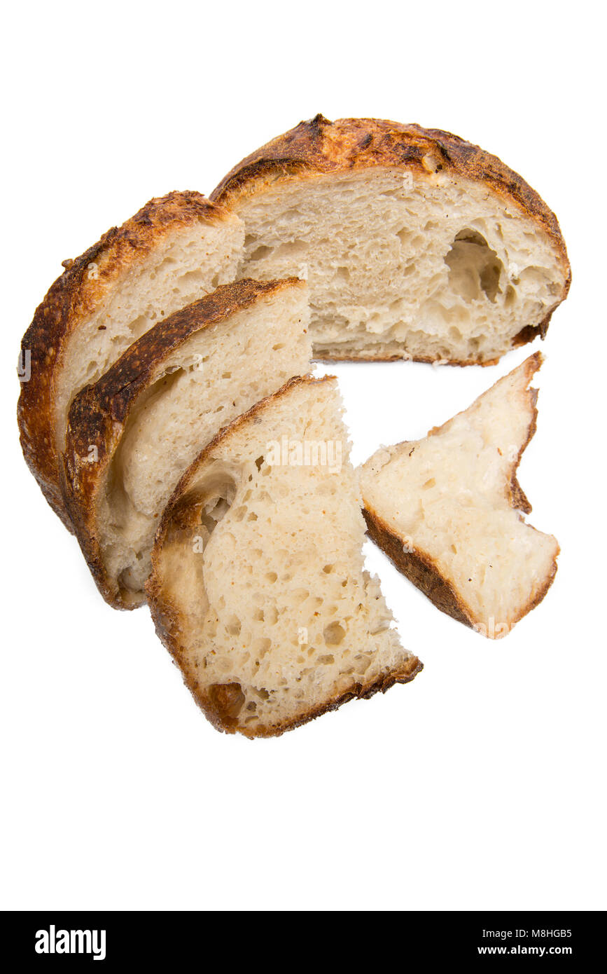 Freshly cut slices of white artisan sourdough bread on isolated a white background. - Stock Image