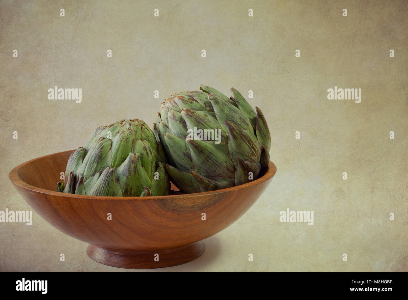 Two artichokes in wooden bowl with grunge background and copy space Stock Photo