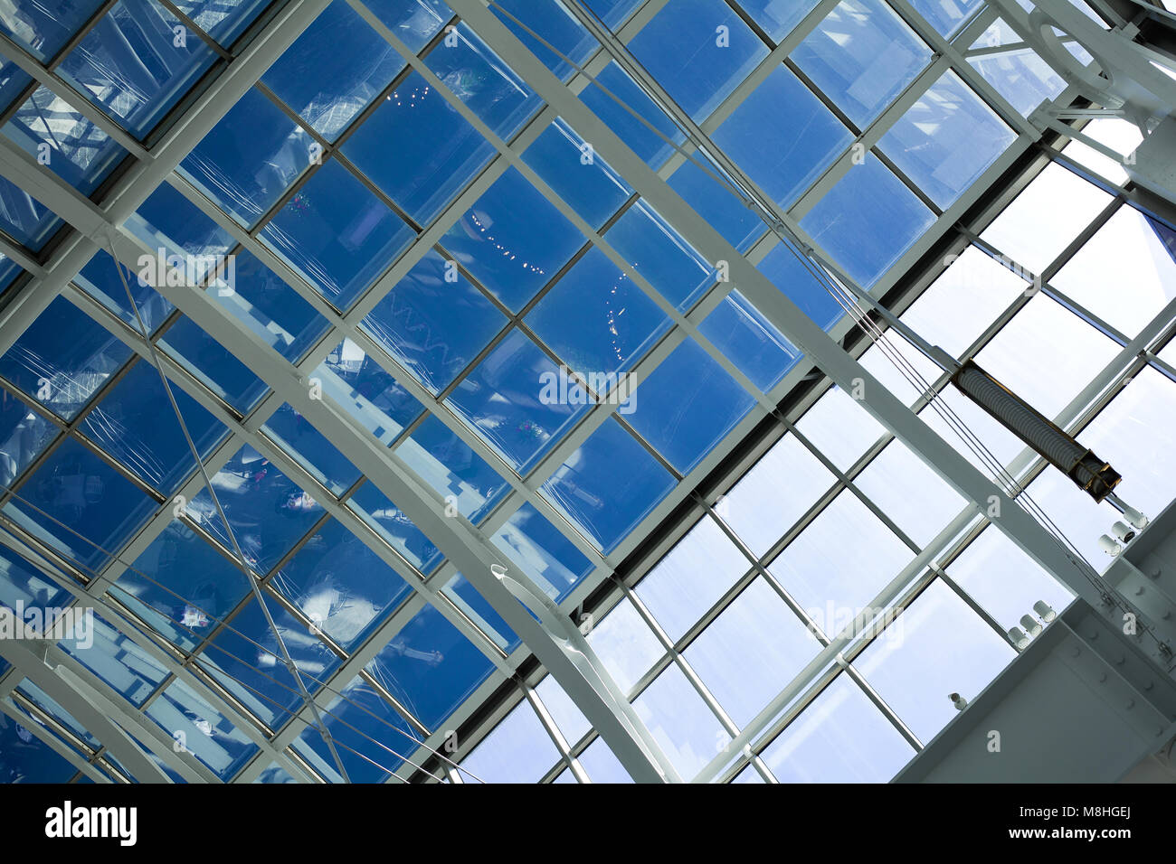 Close-up of glass roof top of modern skyscraper showing reflections from entry level - Stock Image