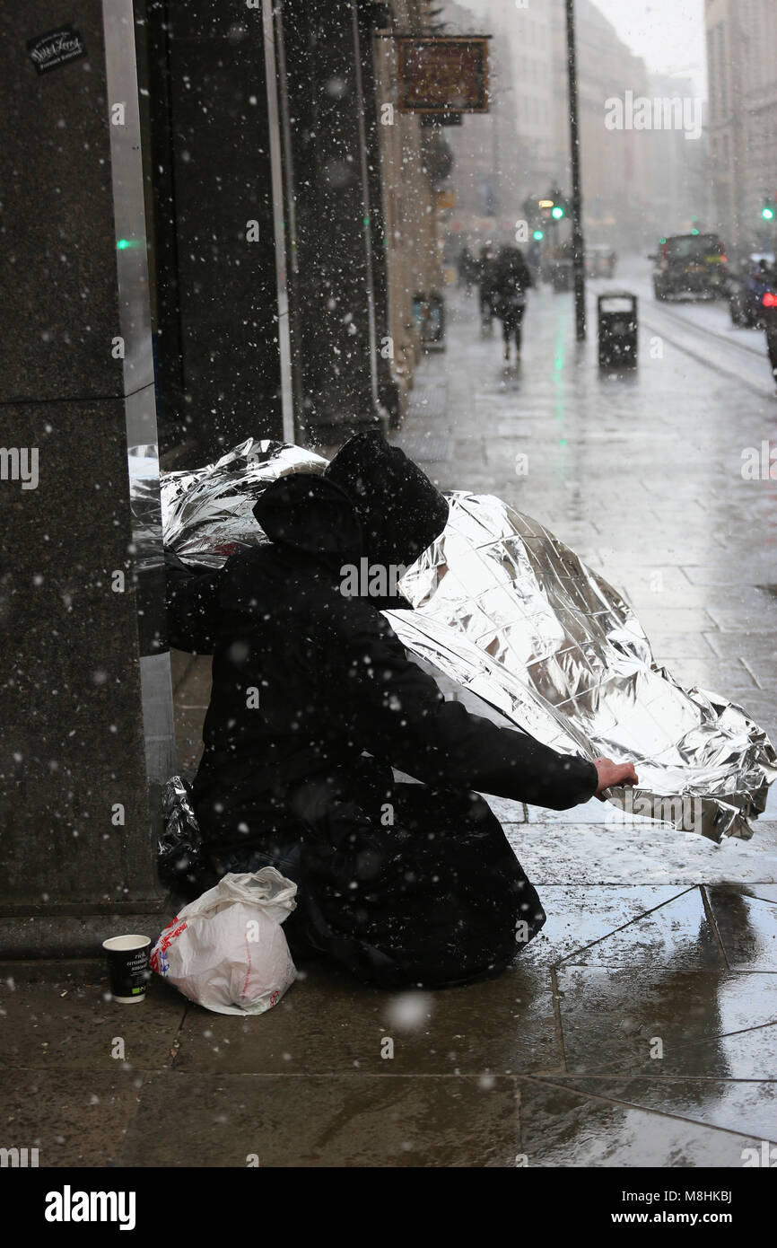 Manchester, UK, 17 Mar 2018. A homeless man unwraps foil to wrap himself in during a snow storm, Manchester, 16th - Stock Image