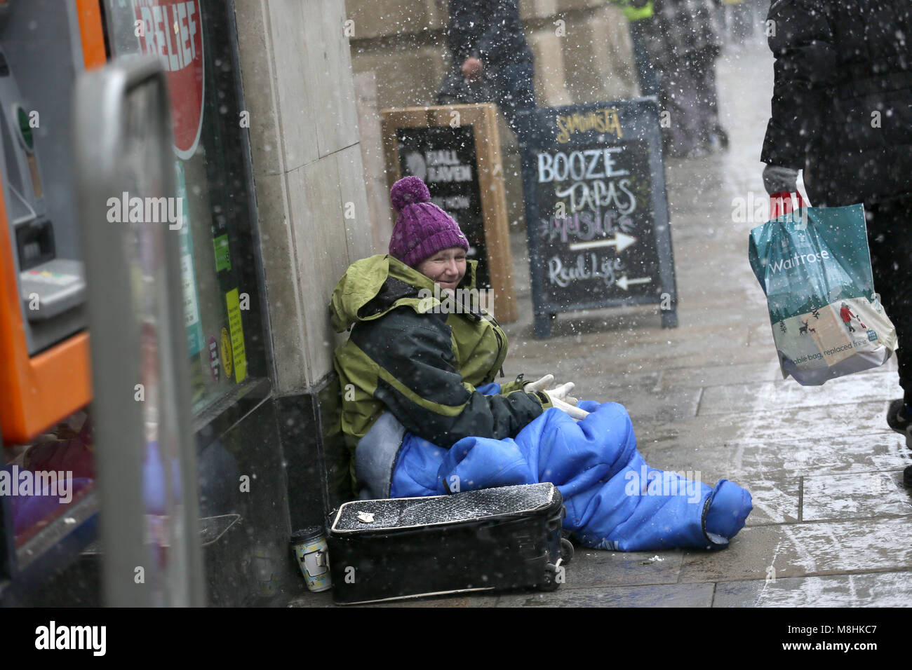 Manchester, UK, 17 Mar 2018. A homeless women sitting on the pavement during snow,  Manchester, 16th March, 2018 - Stock Image