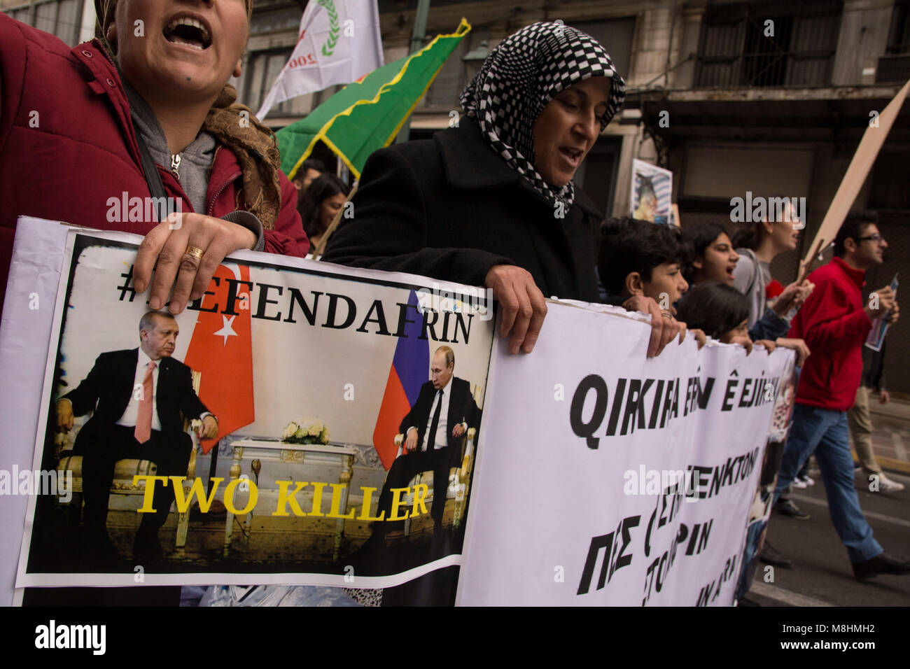 Kurds hold placards depicting the atrocities takingplace in Afrin and shout slogans against Putin and Erdogan. Leftist, - Stock Image