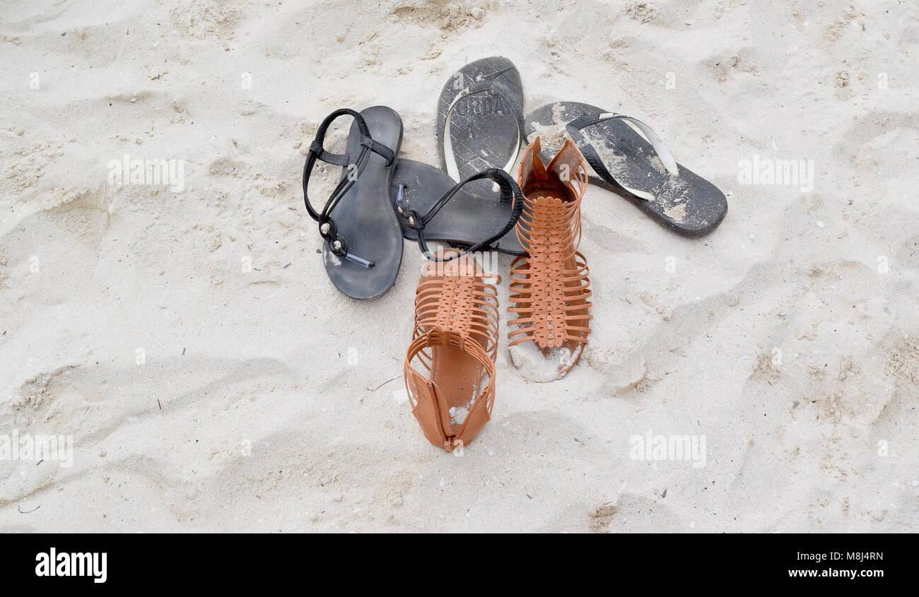 Beach shoes on white sand beach in hot country - Stock Image