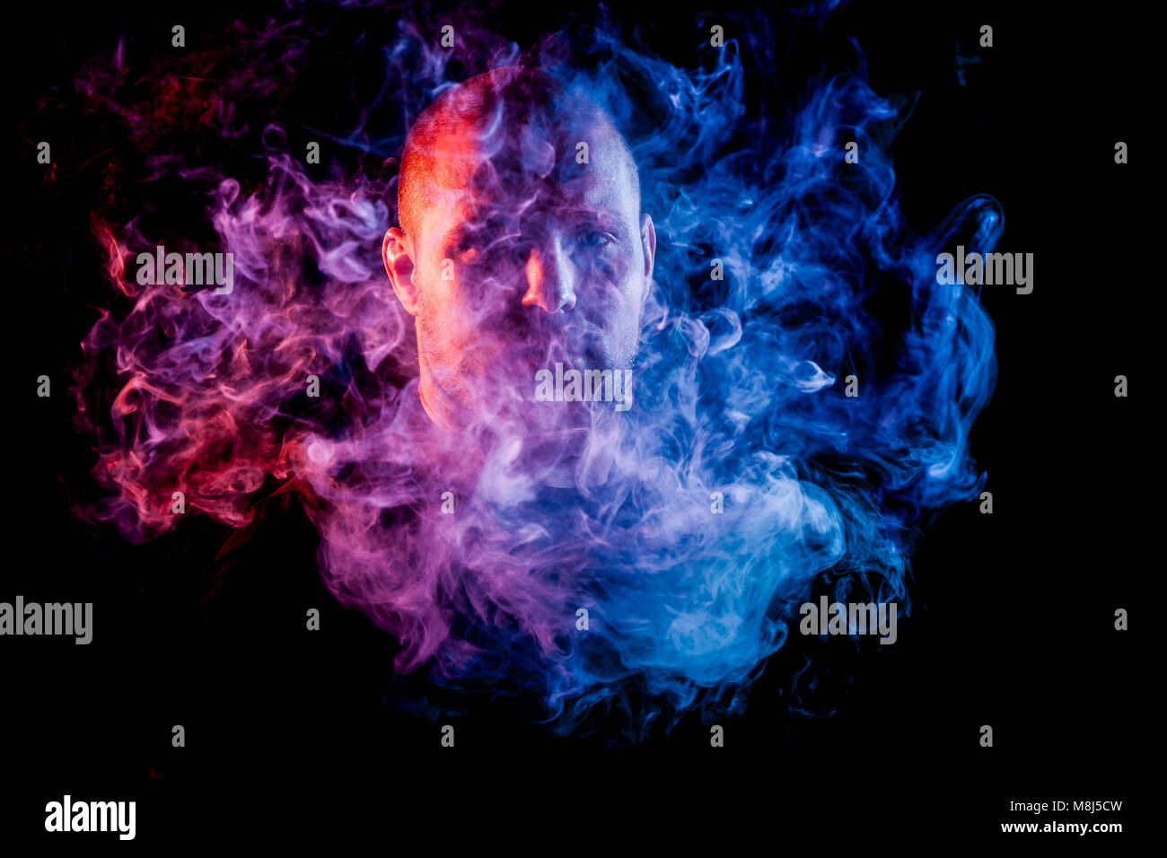 A young man exhales a cloud of colored smoke of blue and pink color on a black isolated. Harm to smoking on the - Stock Image