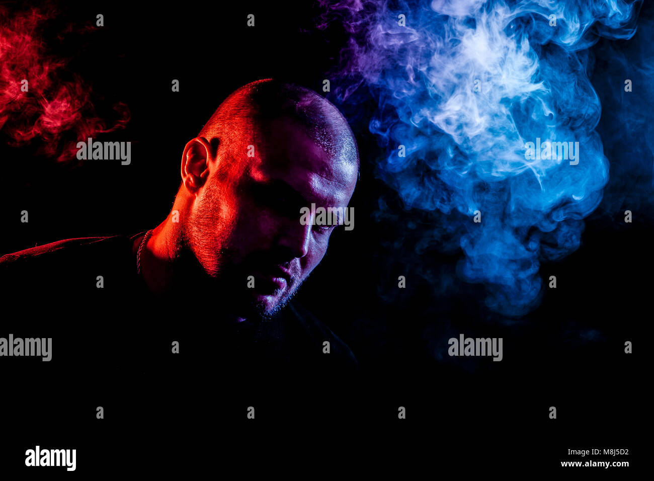A young man exhales a cloud of colored smoke of blue and red color on a black isolated. Harm to smoking on the example - Stock Image
