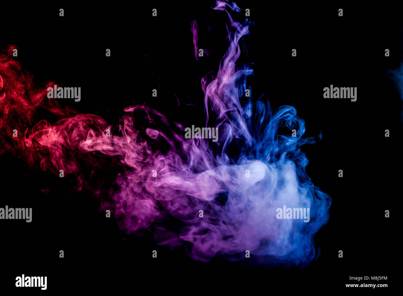 Dense multicolored smoke of pink and   blue  colors on a black isolated background. Background of smoke vape Stock Photo