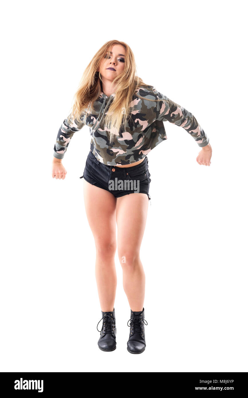 Passionate energetic jazz dancer dancing in military camouflage jacket with clenched fist. Full body isolated on - Stock Image