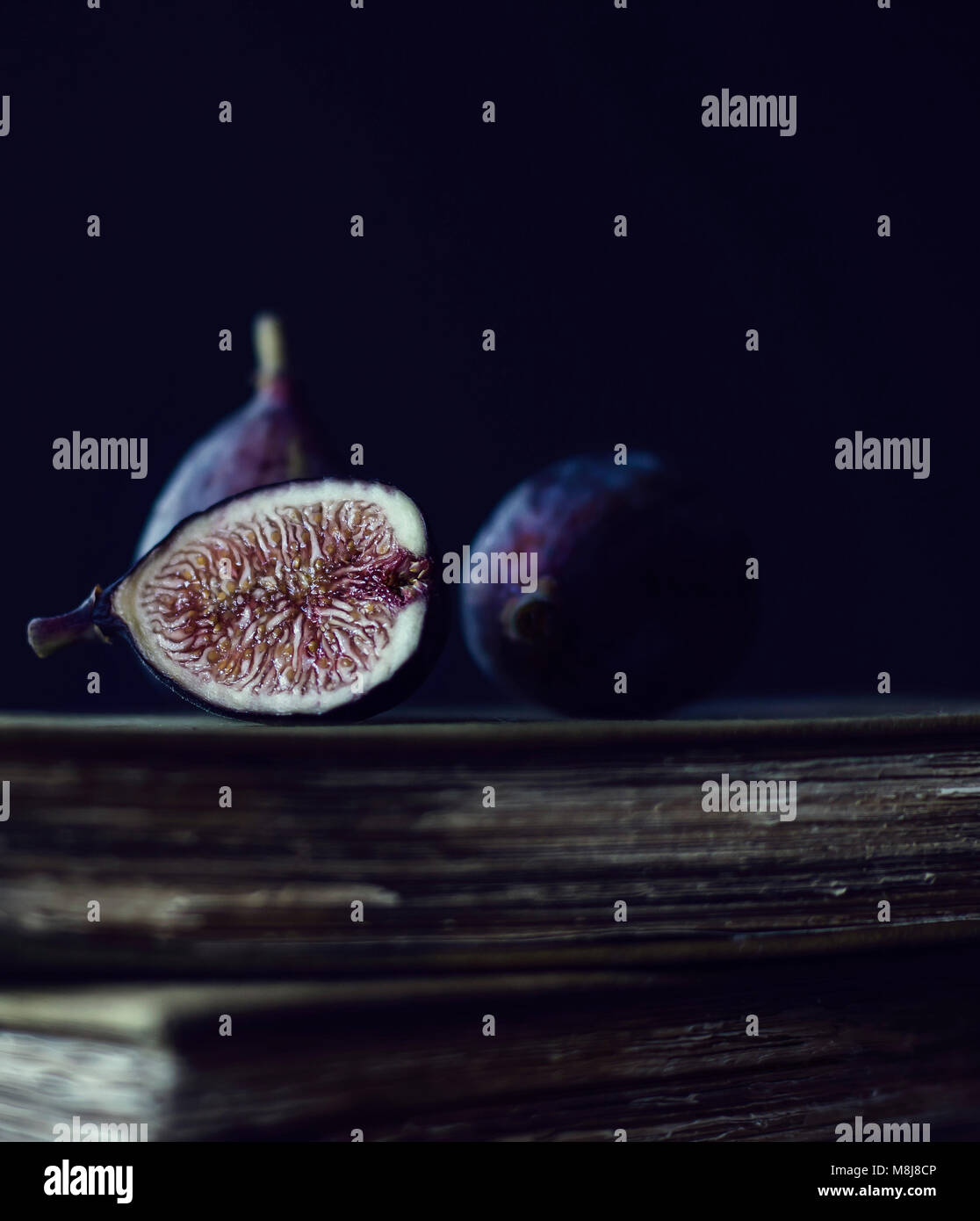 Ripe Figs Positioned on Top of Antique Books - Stock Image