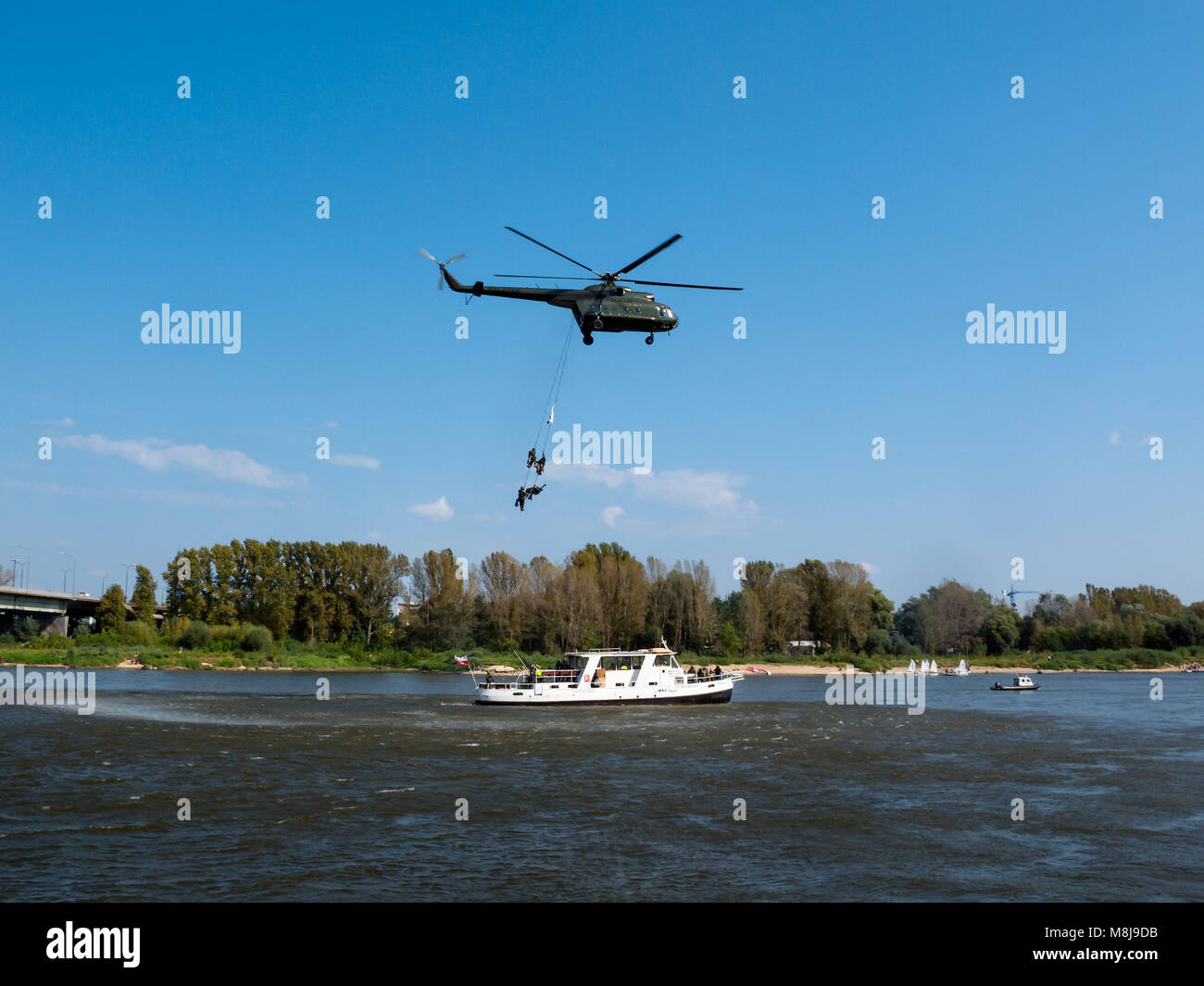 WARSAW, POLAND - SEPTEMBER 13, 2014: Polish GROM Special Forces show boarding a boat with terrorists from a helicopter. Stock Photo