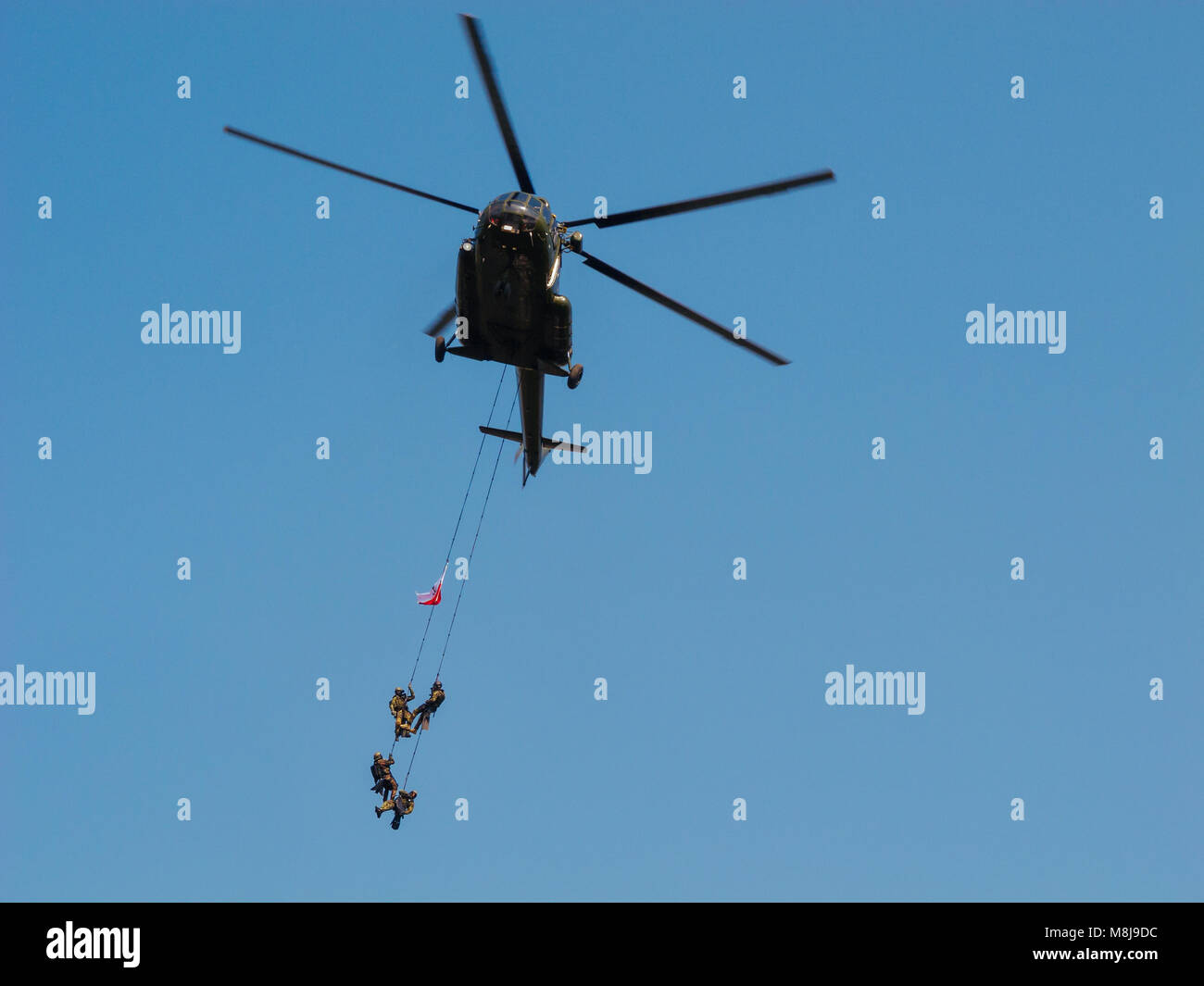 WARSAW, POLAND - SEPTEMBER 13, 2014: Polish GROM Special Forces show off their skills hanging on ropes from a helicopter. Stock Photo