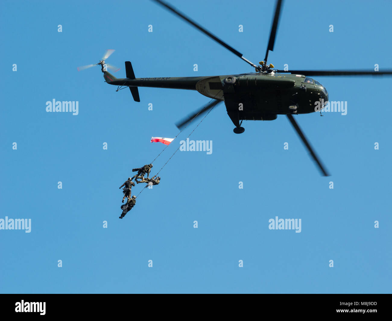 Polish GROM Special Forces show off their skills hanging on ropes from a helicopter. WARSAW, POLAND - SEPTEMBER Stock Photo
