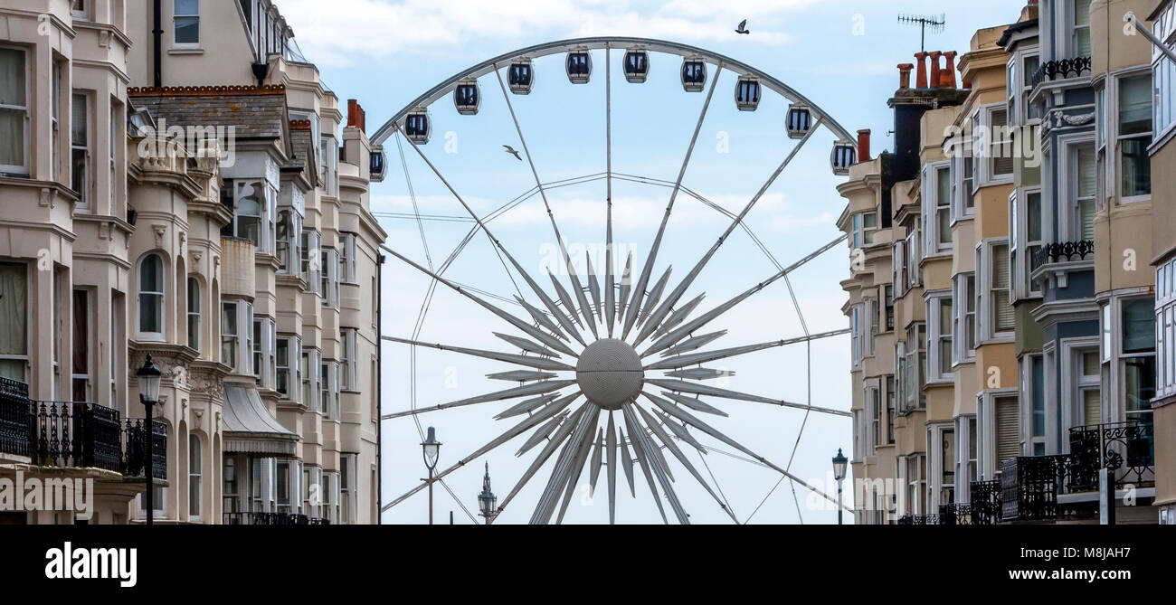 The Brighton Wheel on Madeira Drive as seen at the end of a grand row of Victotrian terraced houses - Stock Image