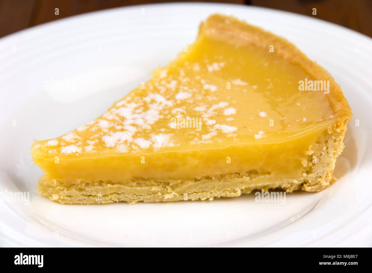 Lemon tart slice on a white plate with a shallow depth of field - Stock Image
