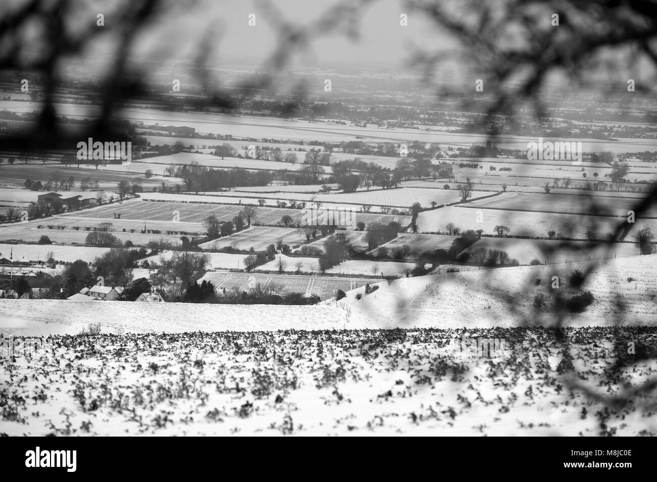 View of the village of Edington which has covered the Wiltshire countryside in Snow. - Stock Image
