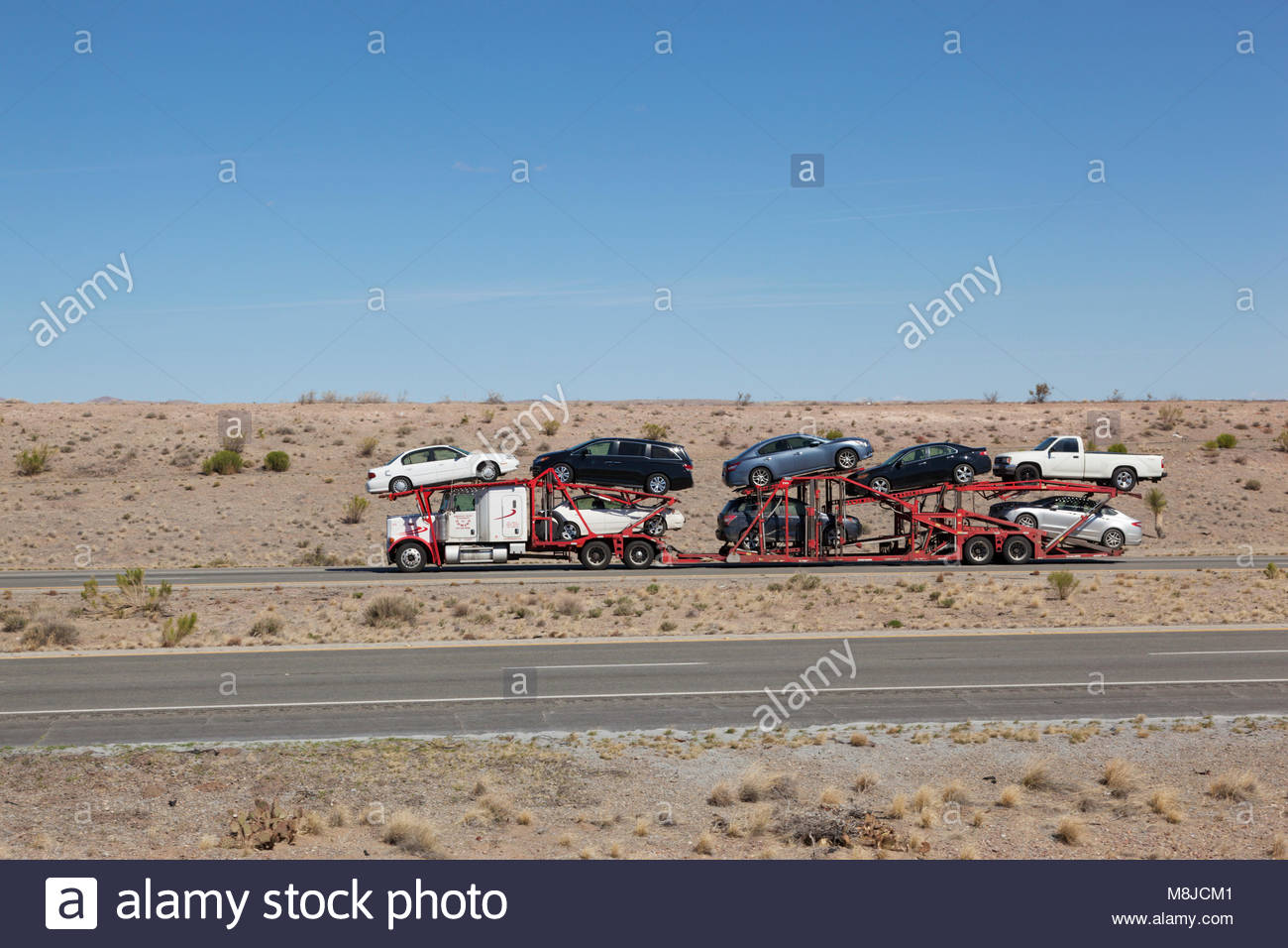 Semi-tractor with car hauler trailer loaded with automobiles on interstate highway in southeastern Arizona, USA, - Stock Image