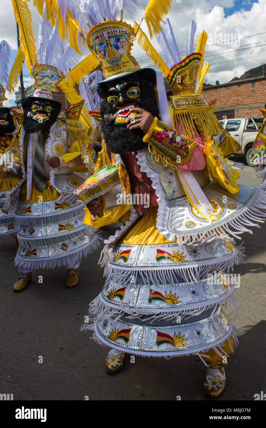 Close-up of man in traditional costume, mask and headdress in yellow and white in festival parade - Stock Image
