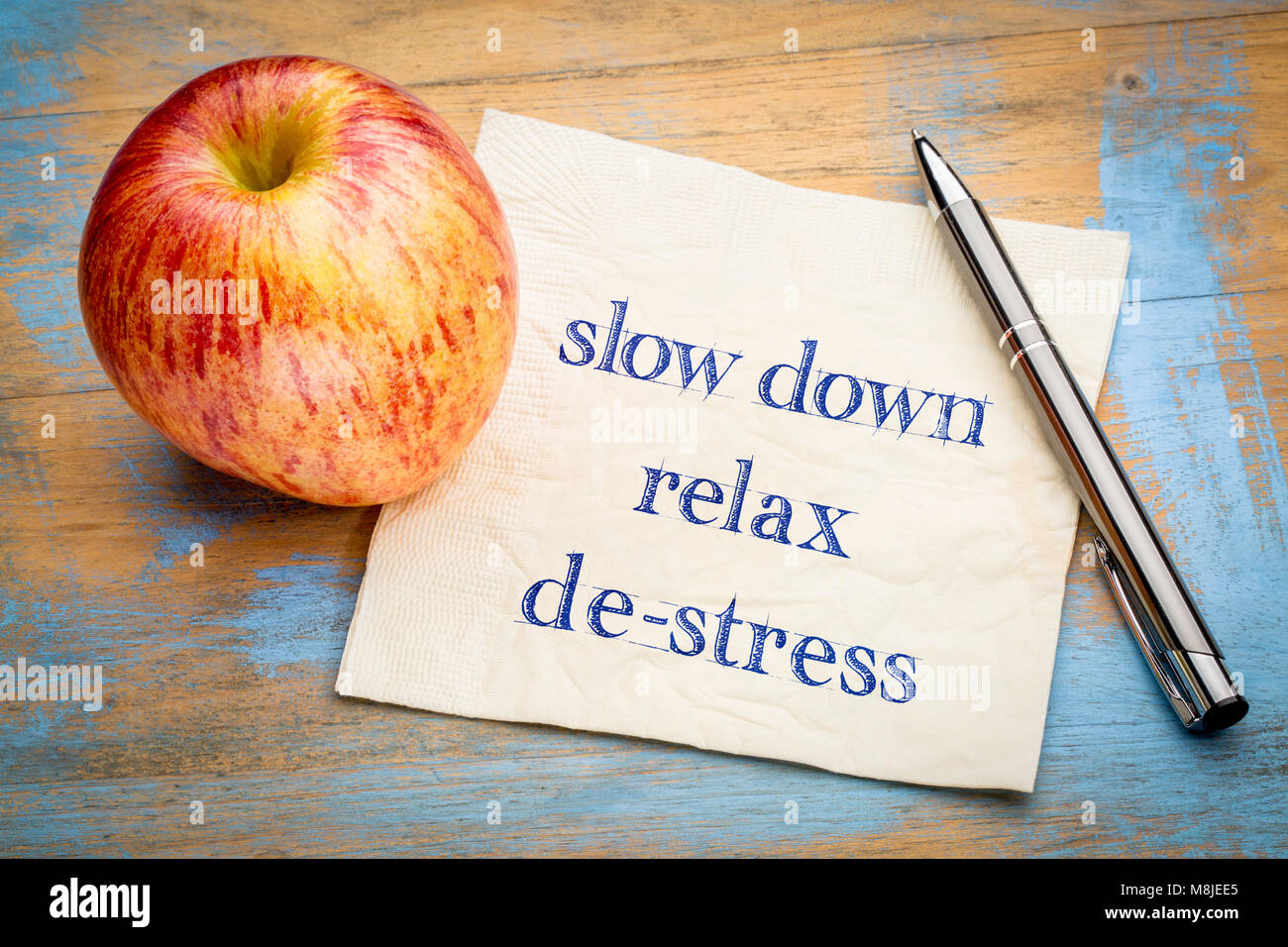 slow down, relax and de-stress - handwriting on a napkin with a fresh apple - Stock Image