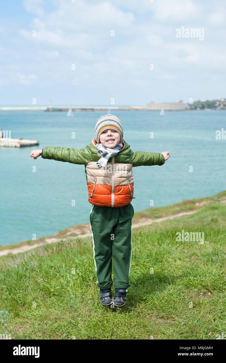 funny small boy dressed in warm jacket scarf and hat jumps on green slope against background of sea harbor in cold - Stock Image