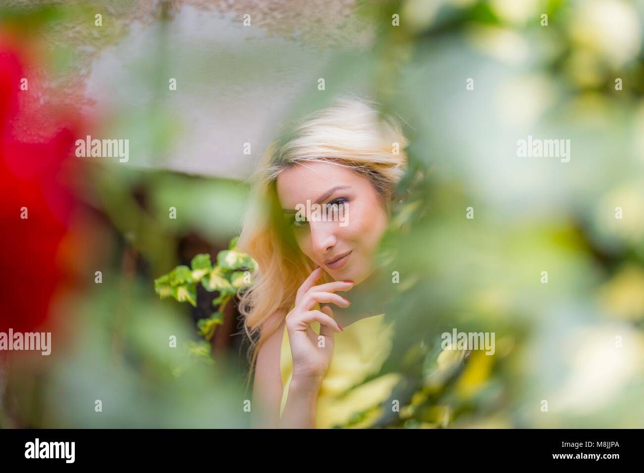 Young woman in nature smiling looking at camera forest trees isolated obscured face - Stock Image