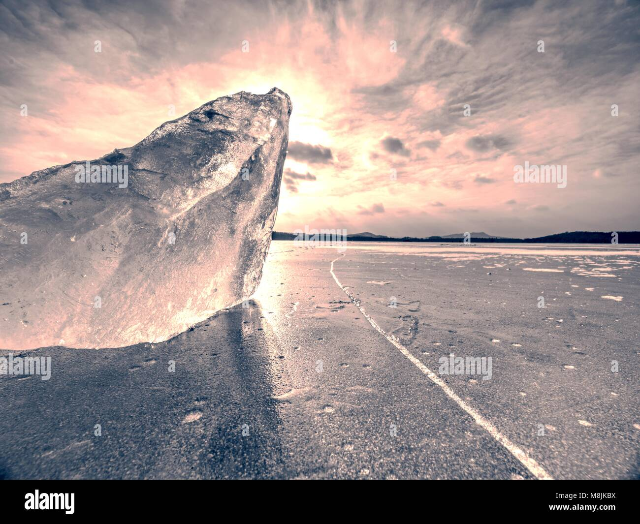 Abstract ice floe on frozen lake, texture of weathered ice and sparkling of evening sun. Deep ice cracks. - Stock Image