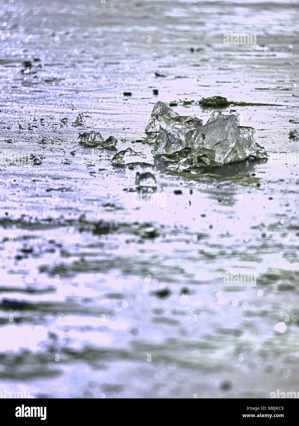 sparkling shards of cracked ice jut out on the frozen lake. The light effect occurs in deep and shallow cracks of - Stock Image
