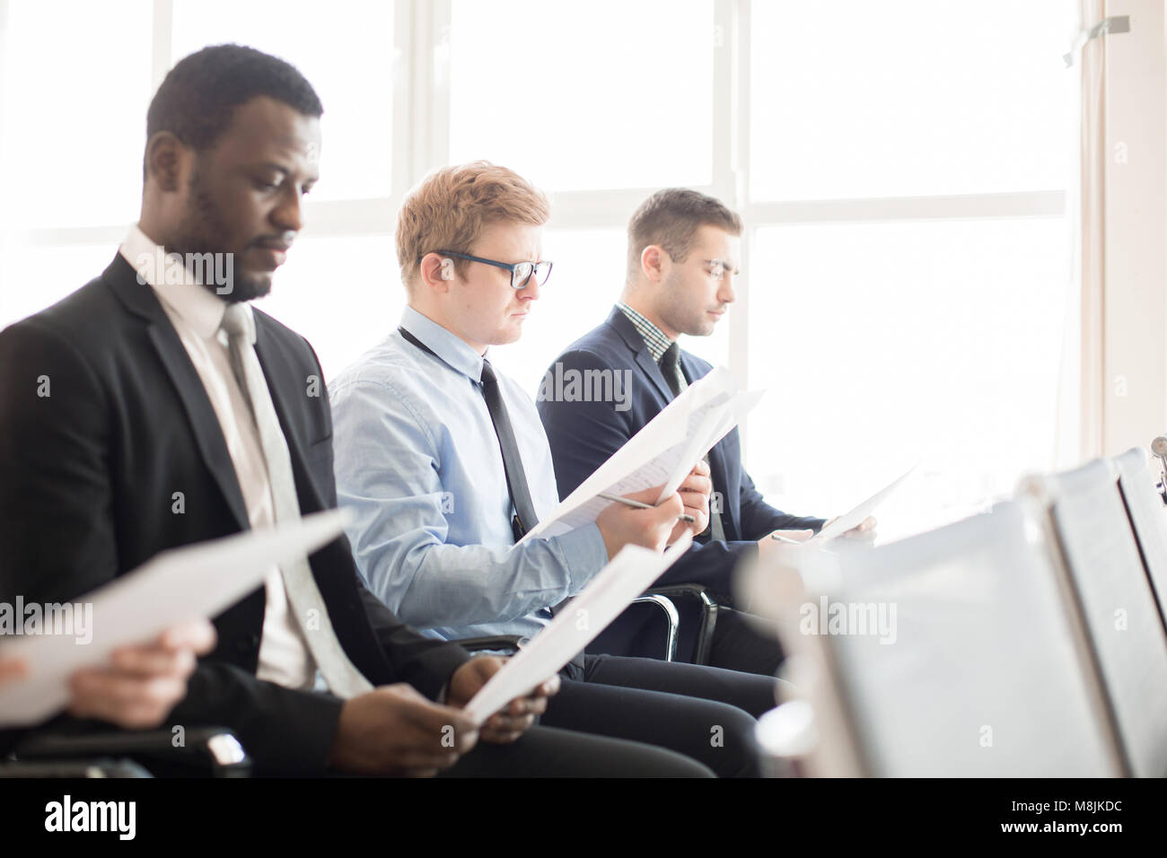 Men reading papers - Stock Image