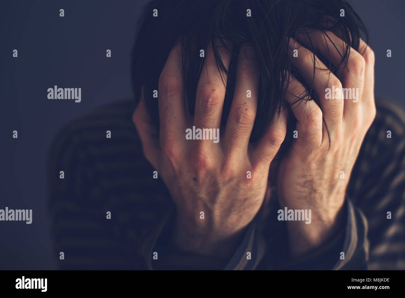 Hopeless drug addict holding his head, low key portrait with selective focus - Stock Image