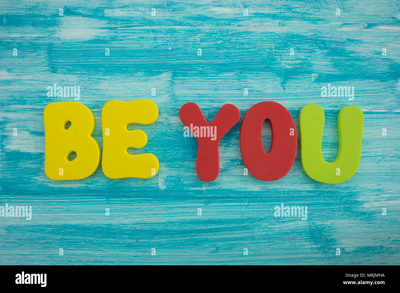 Be You in capital letters on blue colour wash wood background - Stock Image