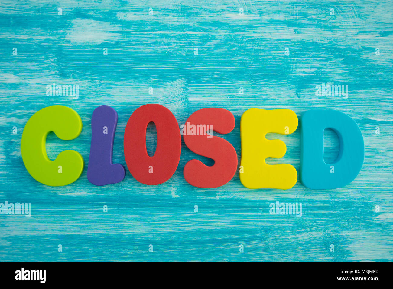 Closed in capital letters on blue colour wash wood background - Stock Image