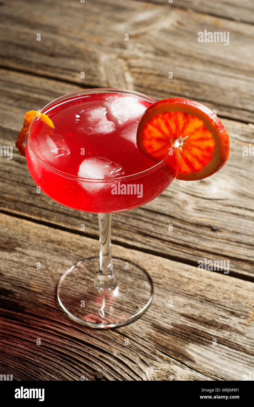 Cold refreshing summer cocktail in a glass on a rustic wooden vintage background - Stock Image