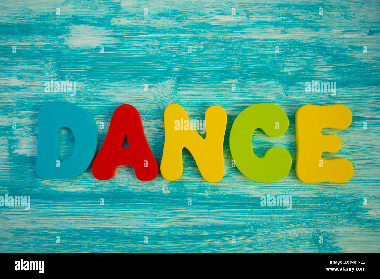 Dance in colourful letters on painted blue wood panel background - Stock Image