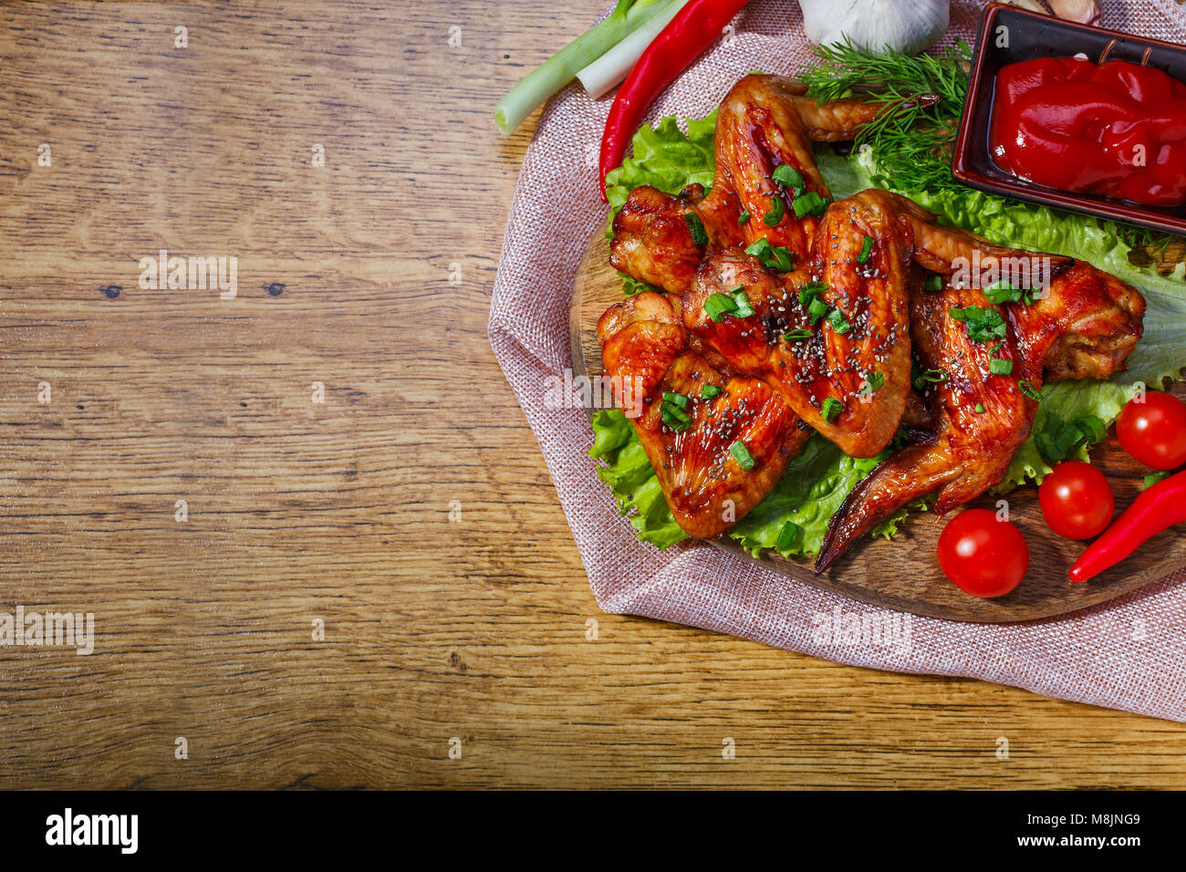 Fried chicken wings and fresh vegetables on wooden table, with space for text - Stock Image