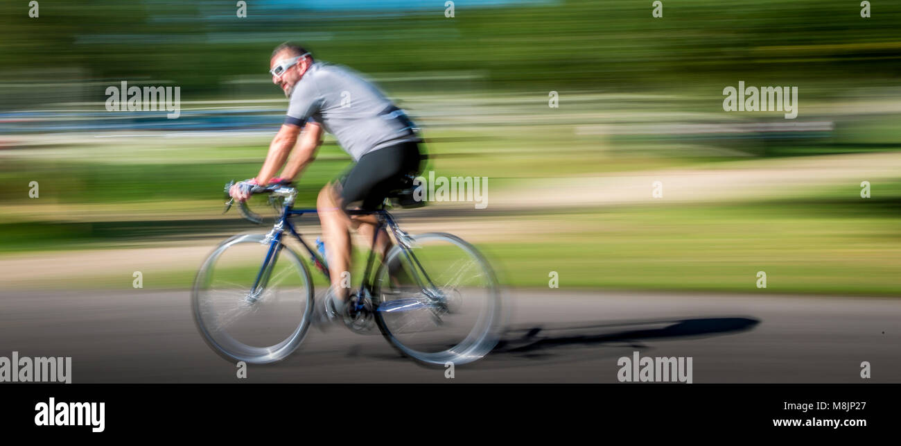 Cyclist wearing white sunglasses races around Richmond Park in a blur - Stock Image