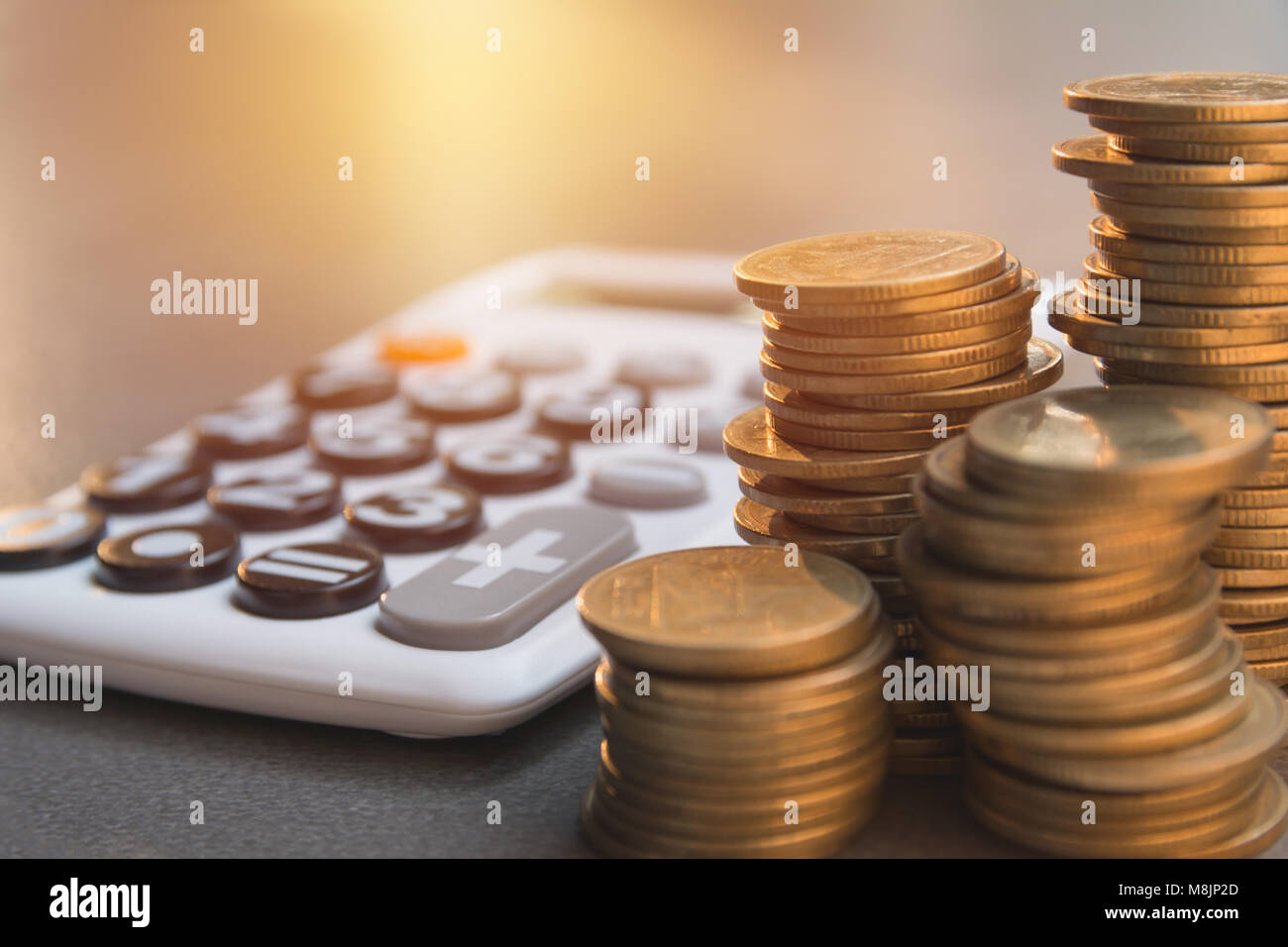 Saving money concept with money coin stack growing and calculator for business and accounting concept. - Stock Image