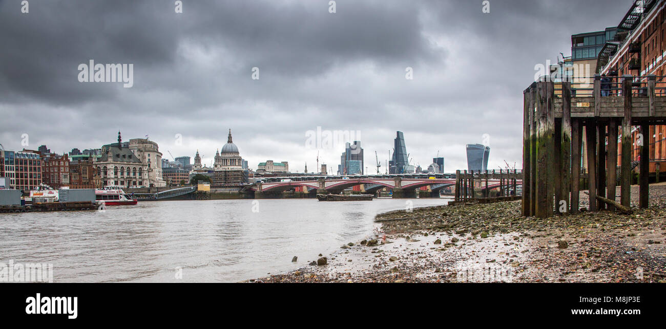 An angry ominous sky hangs over London's River Thames at low tide Stock Photo
